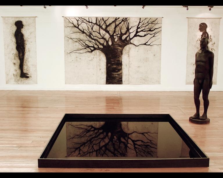 Instalacion Quién me habita, 2004 talla de madera 180x60x40cm dibujos al carbon espejo de agua.jpg